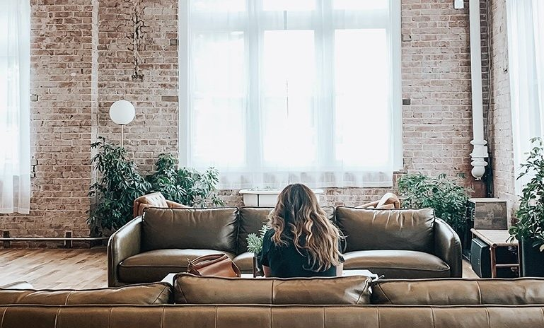 woman sitting on a leather sofa in a loft
