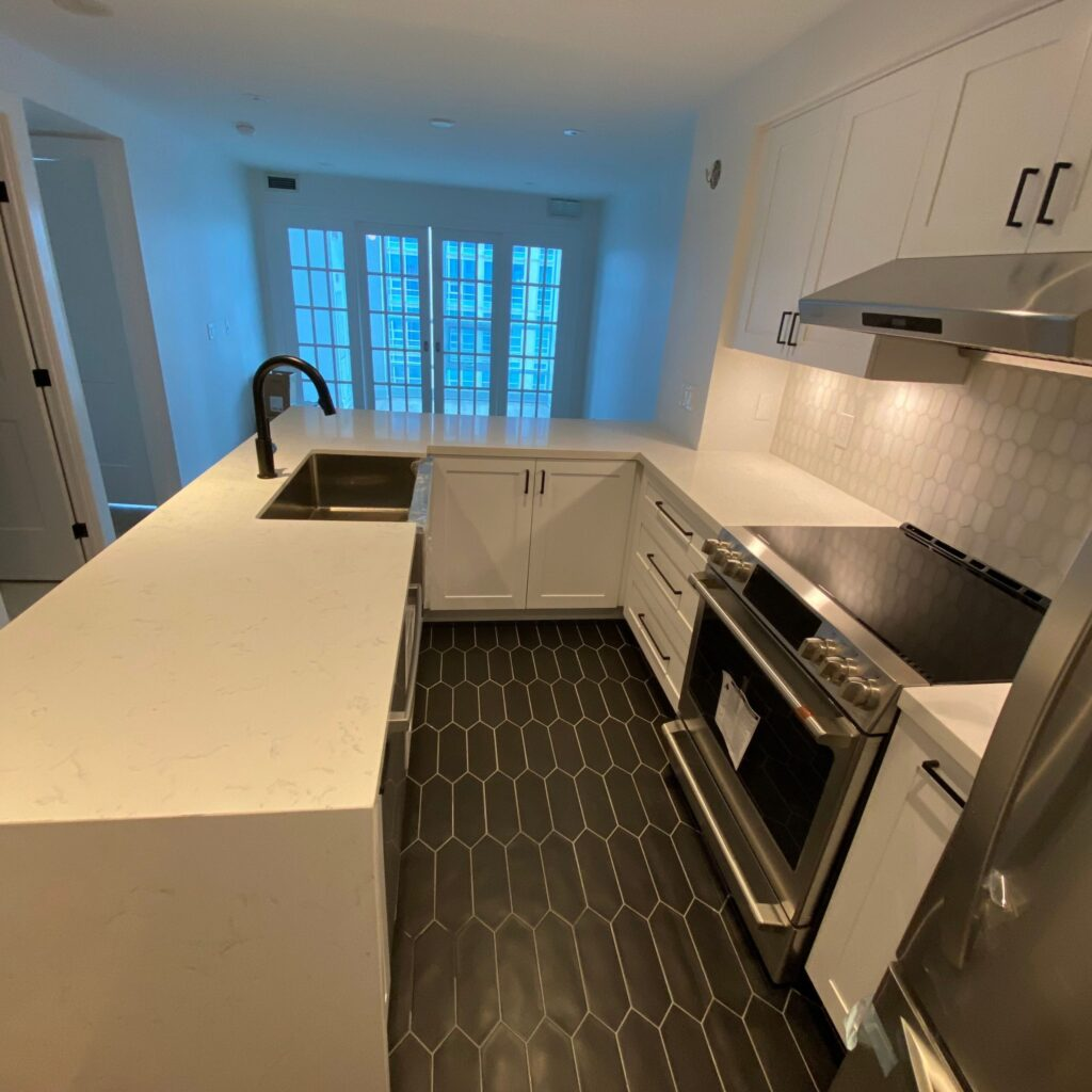 condo kitchen with black floor and white cabinets