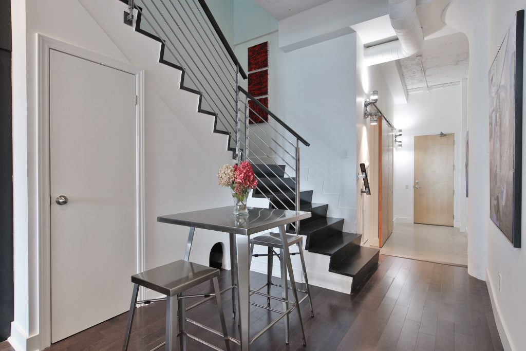steel railing and wooden stairs in second floor staircase - condo upgrade ideas