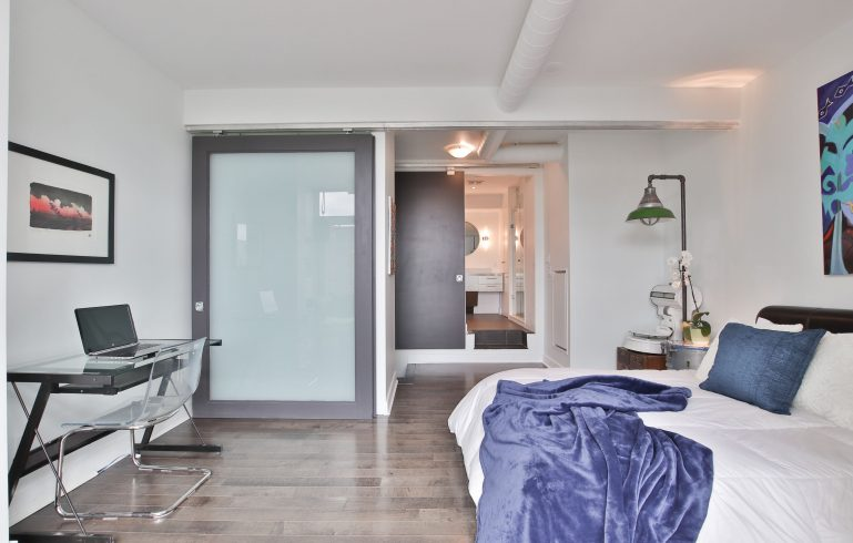 classic bedroom with wooden floor and small bathroom - condo remodel